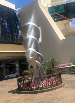 The new stainless steel sculpture outside The STRAT features three figures that face toward the very top of the building.