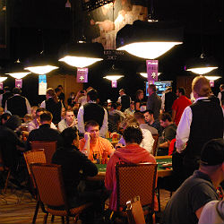 Dealers stand up during hand-for-hand play on the money bubble.