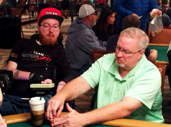 Kenneth Cleeton peels the hole cards over for his son KL to see during Day 2C play at the WSOP Main Event.