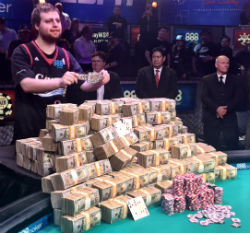 New WSOP Main Event champ Joe McKeehen shows off his stack of money and new gold bracelet.