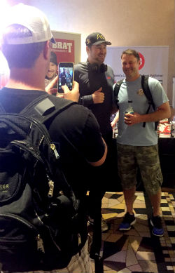 Phil Hellmuth happily poses for pictures with fans during his book signing at the World Series of Poker.