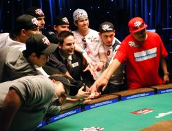 The November Nine surround WSOP Tournament Director Jack Effel and reach for their ultimate prize: the Main Event bracelet.